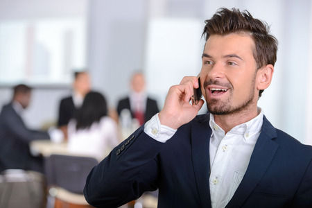 Portrait of a young businessman, people group in background at modern bright office indoors photo
