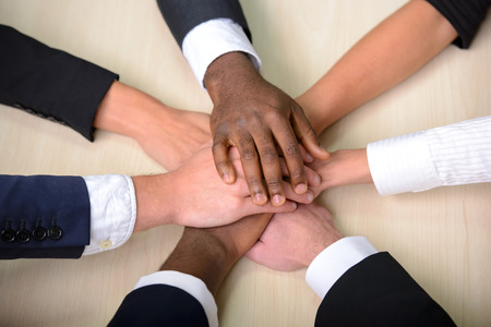 team power: Celebrating victory. Group of business people joining hands. Stock Photo