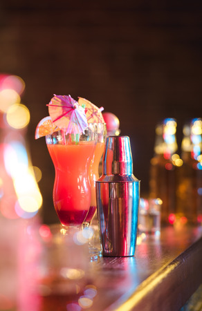 Different alcohol drinks and cocktails on bar. colored light photo