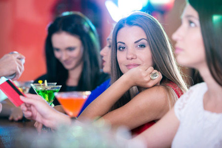 Party, celebration, friends, bachelorette and birthday concept. beautiful womans in evening dresses with cocktails. pay payment card photo