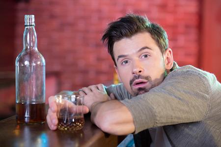 Jonge dronken man drinken van alcohol in de bar