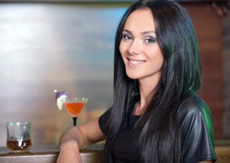 Beautiful cheerful girl with cocktail in bar, at a party photo