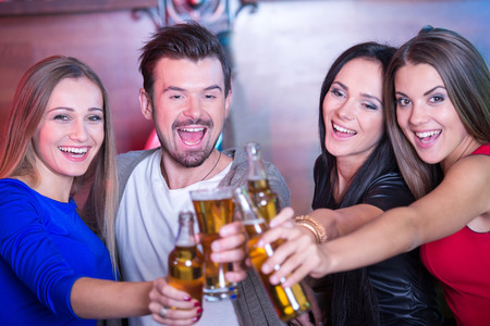 drinking alcohol: Portrait of happy friends holding glasses with cocktails in bar Stock Photo