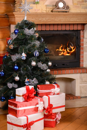 Christmas tree and boxes with gifts for family, fireplace background. photo