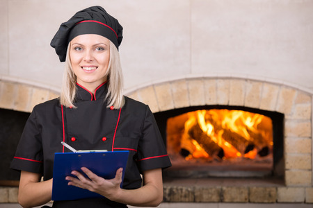 comely: Comely woman, chef baker in black uniform, is writing something on the paper.