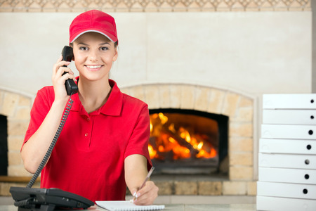 Smiling delivery woman of pizza holding pen and diary for placing order by phone. Foto de archivo