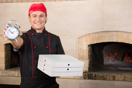 Cook in black uniform and hat with boxes of pizza and clock. photo