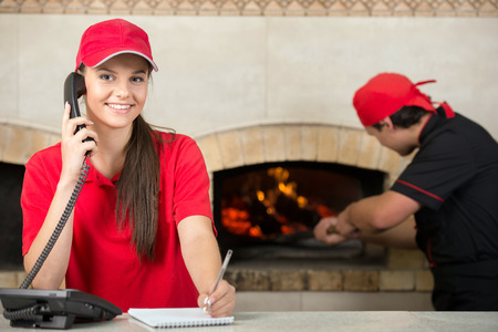 pizzas: Pizza delivery service and chef puts the pizza inside the wood oven to bake.