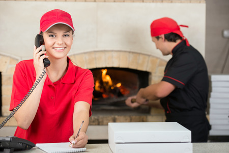 Smiling delivery woman of pizza on the phone and chef baker with long handled bread pan baking pizza into wood fire oven done. photo