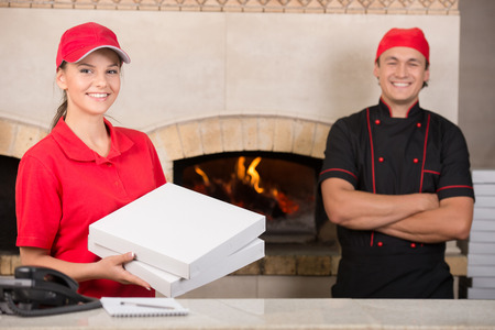 Delivery woman with boxes of pizza and chef. photo