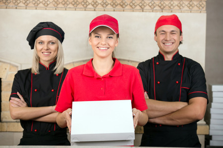 Delivery woman with boxes of pizza and two happy chef. photo