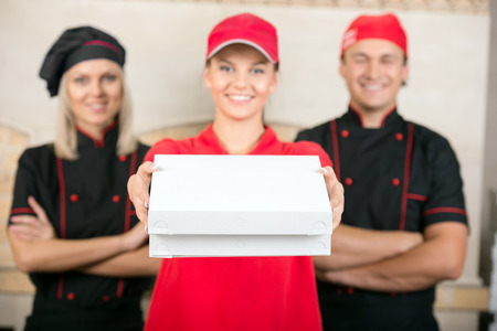 Delivery woman with boxes of pizza and two happy chef in black uniform. photo
