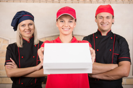 Portrait of delivery woman and two cooks. photo
