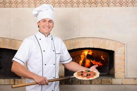 inserts: Cook inserts a pizza in the oven.