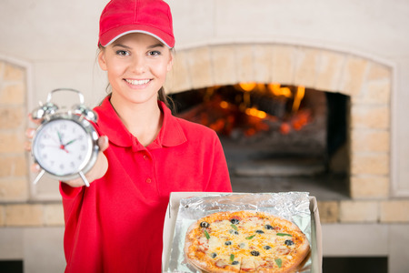 Beautiful delivery woman with delicious pizza in pizza box and clock. photo
