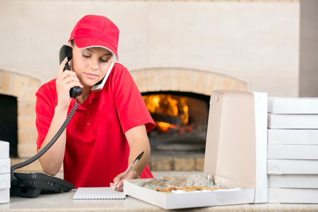 Woman in red is working as delivery girl in a pizza place holding. photo