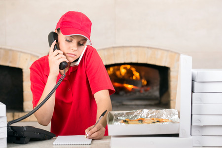 Delivery woman of pizza is taking orders by phone. photo