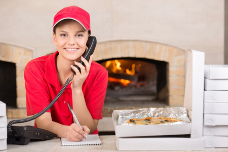 Smiling delivery young woman of pizza on the phone. The boxes of pizza on the table. photo
