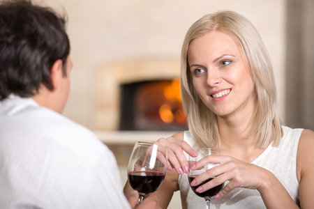 Beautiful young couple in love, couple having fun are talking in cafe and drink wine. photo