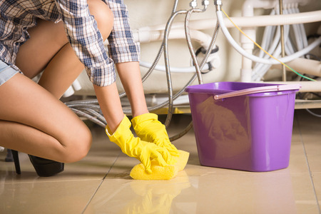 Woman is cleaning the floor. A bucket of water. Stock Photo