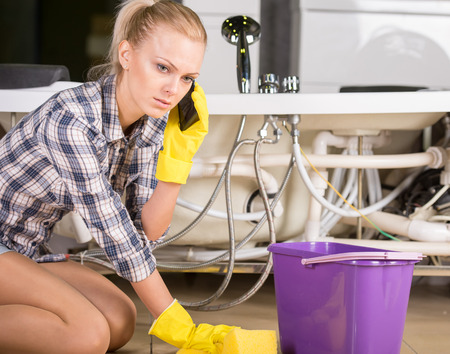 Woman mopping up. She is calling to plumbing. Stock Photo - 32695577