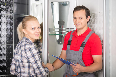 Young woman and plumber are looking at the camera while standing in the bathroom. Stock Photo