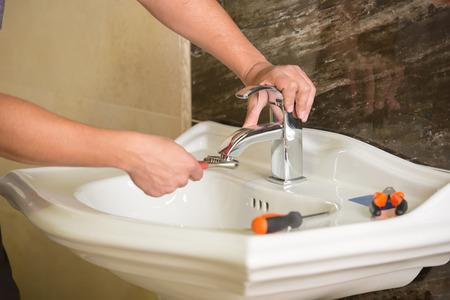 Plumber is repairing an hot-water heater in bathroom. photo