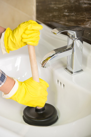 Plumber is cleaning sink with plunger. photo