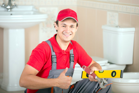 Plumber with the building level and wrench during the work. photo