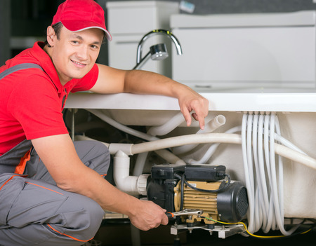 Image of young pretty plumber at work. photo
