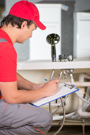Plumber standing in front of washbasin writing on clipboard. photo