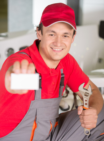 Plumber is holding a spanner in hand and showing business card. photo