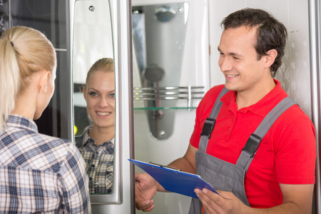 Young woman is looking in the mirror, plumber is smiling. photo