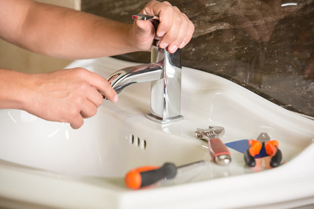 Plumber está reparando un grifo con agua en el baño