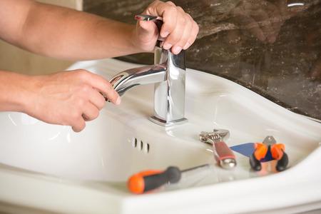 fontanero: Plumber est� reparando un grifo con agua en el ba�o