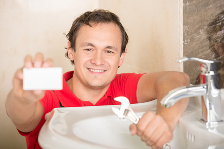 Plumber is holding a business card, sitting next to sink. photo