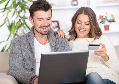 Young couple using a laptop computer at home photo