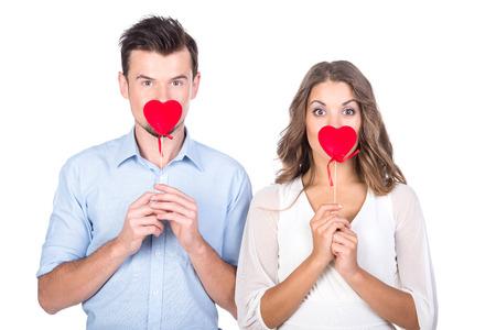 Verliefde paar. Mooie jonge verliefde paar houden papier harten en glimlachen terwijl geïsoleerd op wit Stockfoto