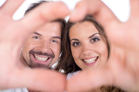 gestos: Pareja de San Valent�n. Retrato de muchacha sonriente belleza y su novio haciendo forma de coraz�n hermoso por sus manos. Familia feliz alegre. Concepto del amor. Muestra del coraz�n. Riendo amantes felices. D�a De San Valent�n