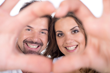 gestures: Valentine couple. Portrait of smiling beauty girl and her handsome boyfriend making shape of heart by their hands. Happy joyful family. Love concept. Heart sign. Laughing happy lovers. Valentines Day