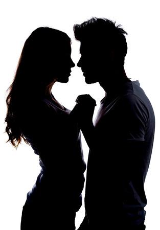 enamorados besandose: Silueta de una pareja feliz celebraci�n de unos a otros Foto de archivo