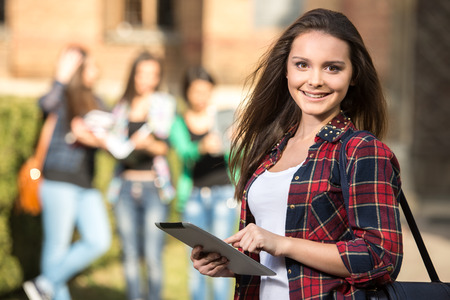 Young handsome female student at the college, outdoors.