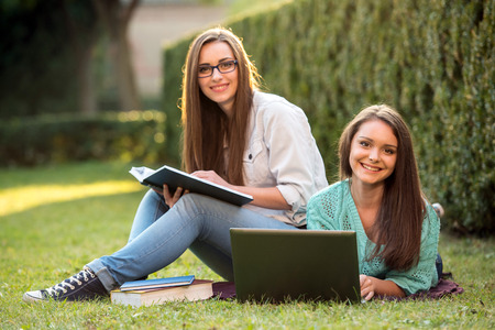 Two smiling female students are sitting on the grass with laptop at campus. They are looking at camera. Stock Photo