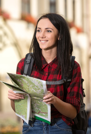take a history: Young pretty woman, tourist with backpack, and touristic map in the town.