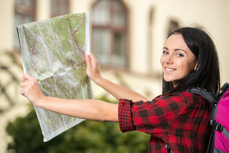 take a history: Young pretty woman, tourist with touristic map in the town, looking at the camera.