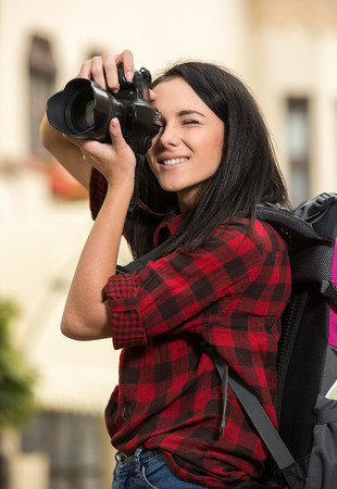 take a history: Young handsome woman in the town is taking a picture.