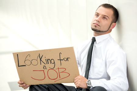 looking for a job: Unemployment. Young businessman is squatting with sign Looking for a job, outdoors.