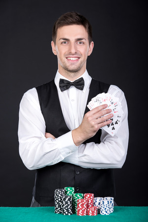 croupier: Portrait of a young smiling croupier with gambling chips on the green table and playing cards.