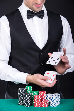 croupier: Portrait of a croupier with gambling chips on the green table and playing cards.