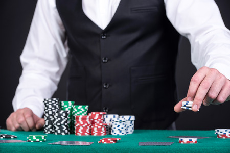 croupier: Portrait of a croupier is holding gambling chips on table. Stock Photo